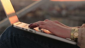 Close-up of young businesswoman using laptop outdoors. Woman hands with manicure typing close up with cityscape stock video