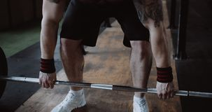 Close-up young Caucasian athlete man lifting heavy barbell in large hardcore gym hall. Ambition and challenge concept. Muscular male professional sportsman stock video