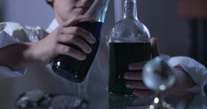 Close-up of young caucasian chemist mixing chemicals. Curly-haired boy in lab coat holding flasks filled with liquids