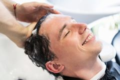 Close-up of a young caucasian man having his hair washed in a hairdressing salon. royalty free stock photos