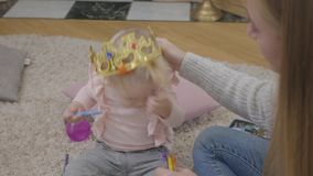 Close-up of young caucasian mother trying to put toy crown on daughter's head. Pretty blond baby girl sitting at soft stock video