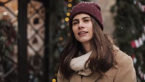 Close up of young caucasian pretty girl wearing winter hat walking. Woman looking up while snow is falling at Christmas stock video footage