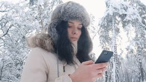 Close up of young caucasian woman in a warm hat using a smartphone in winter snowy forest. Close up young caucasian woman using a smartphone in winter time stock video