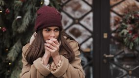 Close up of young charming brunette girl wearing winter hat looking aside, smiling, warming and rubbing her hands. Close up of young charming brunette girl stock footage