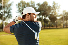 Close up of a young concentrated man shooting golf ball royalty free stock images