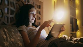 Close-up of young concentrated woman using tablet and watching online news lying in bed at home at night Stock Photo