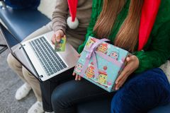 Close-up of a young couple with a credit card, laptop and gift box. Close-up of a young couple on the couch, a men is holding a credit card and a laptop, a gift stock photo