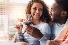 Close up of young couple expressing joy. Lovely atmosphere. Close up of joyful young couple drinking wine while looking at each other and showing true emotions stock image