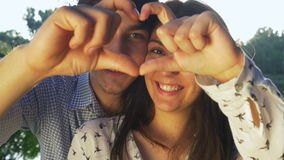 Close-up of young couple making a heart shape at sunset stock video footage