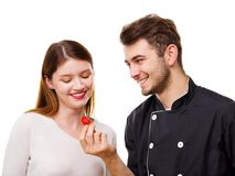 Close-up of a young couple, a man feeding a girl an appetizing strawberry, isolated on a white background stock photo