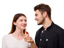 Close-up of a young couple, a man feeding a girl an appetizing strawberry, isolated on a white background stock image