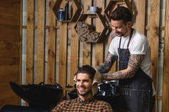 Close up of young customer with wet hair. Barber wipes hair of the client with a towel, against wooden wall royalty free stock image