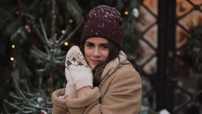 Close up of young cute happy beautiful girl in winter clothes standing in falling snowflakes, smiling, holds hands near stock video footage