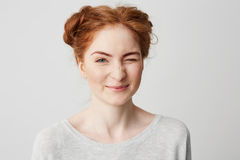 Close up of young cute redhead girl smiling looking at camera winking over white background. Stock Images