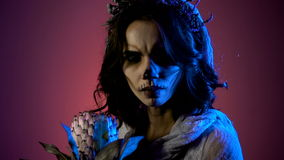 Close up of a young dark-haired girl with halloween creepy make-up. Side view of a dark-haired young woman dressed in stock video footage