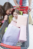 Close-up of young daughter in trolley being pushed by father and mother Stock Image