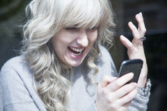 Close up of young desperate and angry woman screaming and talkin. G on telephone Stock Image