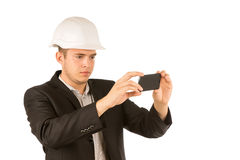 Close up Young Engineer Taking Picture Using Phone. Close up Young Male Engineer in White Helmet and Black Coat Taking Picture Using Mobile Phone. Isolated on Royalty Free Stock Image