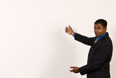 Close up of a young ethnic business man at an off-white projector screen. Young ethnic business man makes a gesture with his arms at an off-white projector Stock Images
