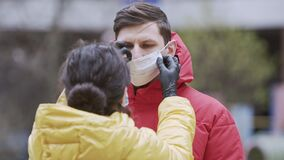 Close-up of young europeans woman put on protective disposable medical face mask on her boyfriend, outdoors. New coronavirus COVI