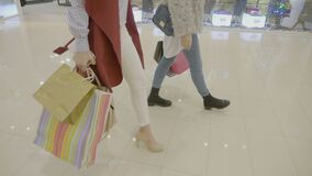Close up of young fashion addict girls wearing heels marching in the mall to do weekend shopping -. Close up of young fashion addict girls wearing heels marching stock video footage