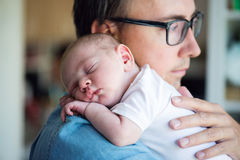 Close up of young father holding his newborn baby son. In his arms royalty free stock images