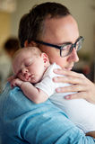 Close up of young father holding his newborn baby son. In his arms royalty free stock image