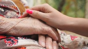Close up of young female arm stroking an elderly hands of old woman. Granddaughter and grandmother spending time stock video footage