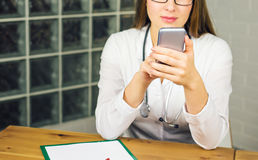 Close-up of young female doctor with smartphone Royalty Free Stock Image