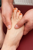 Close-up of young female feet receiving a sole massage Stock Image