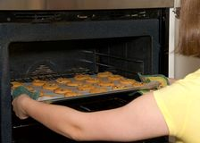 Young woman pulling chocolate chip cookies out of the oven. Close up on young female hands pulling tray of soft and chewy chocolate chip cookies out of the oven Royalty Free Stock Photos