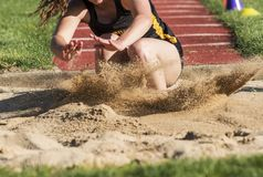 Jumper landing in sand close up. Close up of a young female high school long and triple jumper landing violently in the sand during a competition royalty free stock photo