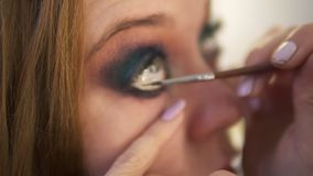 Close up of young female model is being maked up in studio. Artist is applying black liner to lower lid of the right eye stock footage