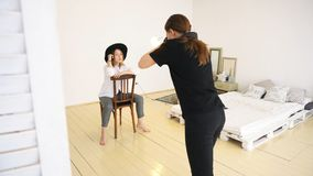 Close-up of young female photographer in black clothes taking pfotos of stylish young woman in black hat, white shirt royalty free stock images