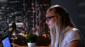 Close-up of young female scientist searching books in Internet late at night. In the background there are skyscrapers stock video