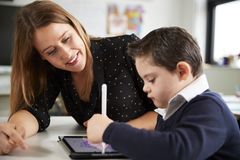 Close up of young female teacher sitting at desk with a Down syndrome schoolboy using a tablet computer in a primary school classr royalty free stock image