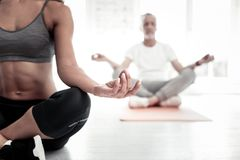 Close up of young female yoga teacher meditating. Everything will be good. Selective focus on a sporty lady wearing sportswear sitting in a lotus position and Stock Photography
