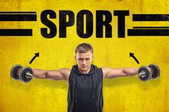 Close-up of young fit man in sleeveless hoody doing side lateral raise with dumbbells against yellow wall with title royalty free stock image