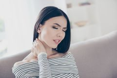 Close up of young frustrated asian lady, having a strong pain in neck. She is at home and alone, sitting on sofa in casual striped Stock Photo