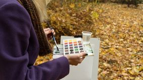 Close-up of young girl artist that paints a picture on the easel in the autumn park. Close-up of young blonde girl artist in purple coat that paints a picture on stock image