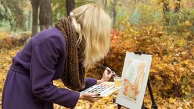 Close-up of young girl artist that paints a picture on the easel in the autumn park. Close-up of young blonde girl artist in purple coat that paints a picture on royalty free stock images