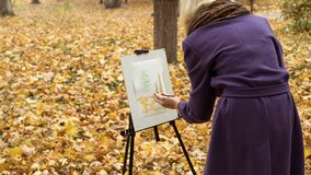 Close-up of young girl artist that paints a picture on the easel in the autumn park. Close-up of young blonde girl artist in purple coat that paints a picture on royalty free stock photography
