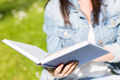 Close up of young girl with book in park Stock Photo