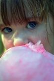 Close up of young girl eating cotton candy Royalty Free Stock Photos