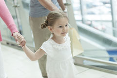 Close-up of young girl holding parents hands stock images