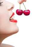 Close up of young girl with red lips eating two berries Royalty Free Stock Photos