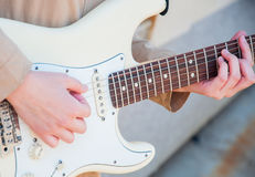 Close up of young girl`s hands playing guitar Stock Images