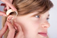 Close up of a young girl& x27;s head and the audiologist& x27;s hands inse Royalty Free Stock Photos