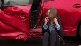 Close-up of girl sitting on the ground near a broken car, she was in an accident. Close-up of a young girl sitting leaning against her broken car after a car stock video