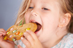 Close Up Of Young Girl Sitting At Table Eating Cookie Stock Image
